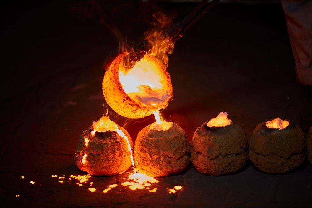 おりんの制作風景。整然と並べられた型に、溶けた合金が手際よく注がれていく。