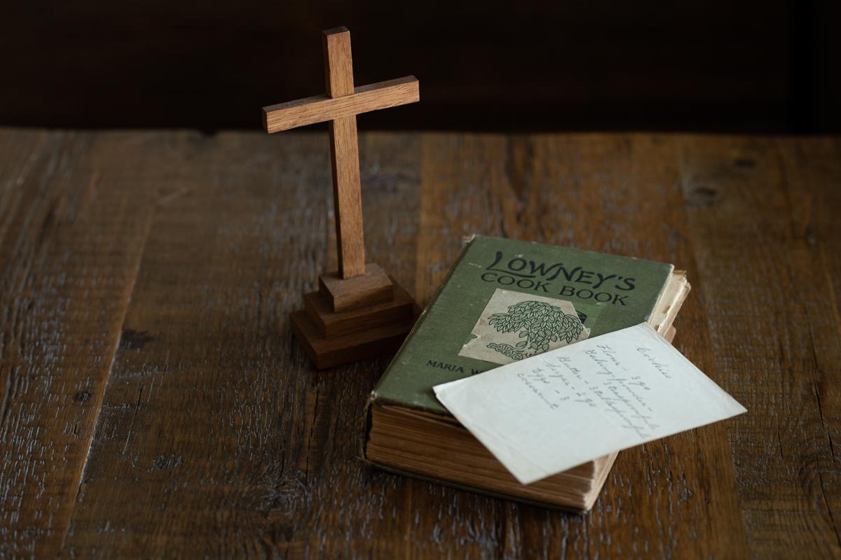 祖母リタの料理本。祖母が手書きした日本料理のレシピもはさみこまれていた。左のウイスキー樽の端材で作られた十字架は、教会に十字架を寄付し、司祭から信者へ渡されたもの。